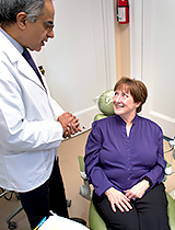 Dentist speaking with smiling female patient