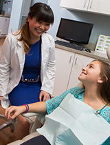 Dentist smiling at teenage patient